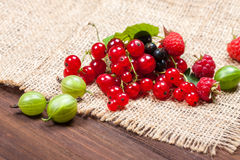 A mixture of ripe berries on a wooden table. Summer Still Life. Raspberries, gooseberries, currants close-up. Royalty Free Stock Images