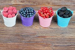 Mixture of summer berries. Mixture of berries in little colorful buckets on brown wooden table Royalty Free Stock Images