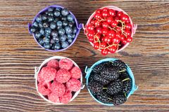 Mixture of summer berries. Mixture of berries in little colorful buckets on brown wooden table Stock Image