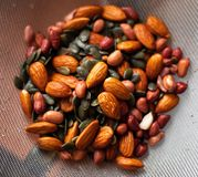 A mixture of wet washed nuts and seeds on the sieve. Peanuts, pumpkin seeds, almonds. A mixture of wet washed nuts and seeds on the sieve. Peanuts, pumpkin seeds stock photo