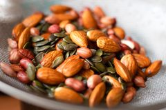 A mixture of wet washed nuts and seeds on the sieve. Peanuts, pumpkin seeds, almonds. A mixture of wet washed nuts and seeds on the sieve. Peanuts, pumpkin seeds stock photography
