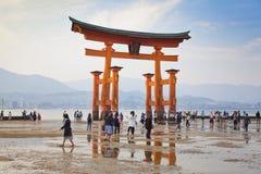 MIYAJIMA, GIAPPONE - 27 MAGGIO: I turisti camminano intorno al portone di galleggiamento famoso di torii del santuario di Itsukus Immagine Stock