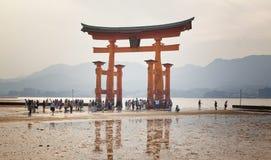 MIYAJIMA, GIAPPONE - 27 MAGGIO: I turisti camminano intorno al portone di galleggiamento famoso di torii del santuario di Itsukus Fotografia Stock