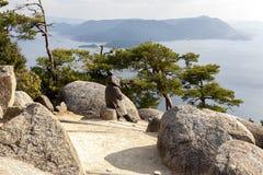 Miyajima, Japan - December 28, 2009: Vrouw die mooie mening over overzees eiland bewonderen Miyajima is een klein eiland buiten d stock afbeelding