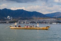 MIYAJIMA JAPAN - FEBRUARI 03, 2018: Turister och lokaler i ett fartyg med två japanska män med skovlar som seglar i havet royaltyfri fotografi