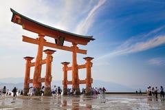 MIYAJIMA, JAPAN - 27. MAI: Touristen gehen um das berühmte sich hin- und herbewegende torii Tor des Itsukushima-Schreins auf SH M Lizenzfreie Stockbilder