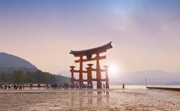MIYAJIMA JAPAN - MAJ 27: Turister går runt om den berömda sväva toriiporten av den Itsukushima relikskrin på Miyajima på sh lågva Arkivbild