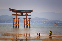 MIYAJIMA, JAPAN - MAY 27: Asian Tourists in front of famous floating torii gate of the Itsukushima Shrine on Miyajima at sunset on Stock Images