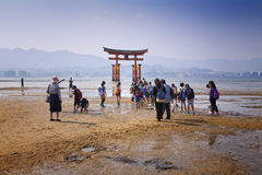 MIYAJIMA, JAPAN - MAY 27: Asian Tourists in front of famous floating torii gate of the Itsukushima Shrine on Miyajima at sunset on Royalty Free Stock Photography