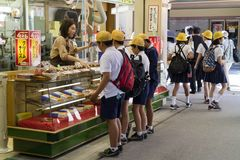 Miyajima, Japan - May 26, 2017:Group of school children in unif. Orm buying gifts and candy in Miyajima on a school trip stock photo