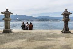 Miyajima Japan - September 14 2017: tre kvinnliga turister på sjösidan av Miyajima arkivbild