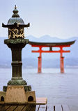 Miyajima temple. Old typical Japanese bronze lantern with hanged paper wishes front of the world wide famous torii of Itsukushima temple in Miyajima island, near Stock Images