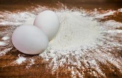 Mjöl med ägg på tabellen royaltyfria foton