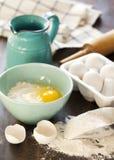 Mjöl och ägg på en trätabell Arkivbild