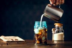 Mjölka att hälla in i med is organiskt kaffe som tjänas som i blåa Mason Jar royaltyfri bild