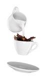 Mjölka att hällas in i den lilla koppen kaffe Vit bakgrund Fotografering för Bildbyråer