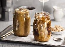 Mjölka att hällas in i ett exponeringsglas av med is kaffe Arkivfoto
