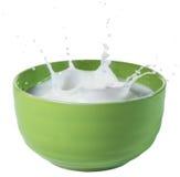 Mjölka att plaska i grön bunke Arkivfoton