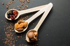 Mjölka choklad med torkade frukter och muttrar i träskedar på en svart bakgrund arkivfoto