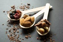 Mjölka choklad med torkade frukter och muttrar i träskedar på en svart bakgrund arkivfoton