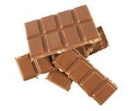 Mjölka chokladstänger med hasselnötter som isoleras på en vit bakgrund Arkivfoto