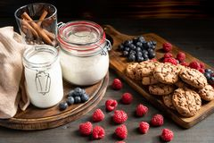 Mjölka, cinnamom, mjöl i förseglade krus, kex och bär som förläggas på trä royaltyfri foto