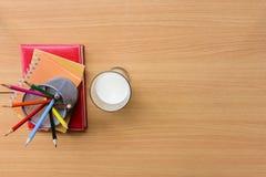 Mjölka exponeringsglas med anteckningsboken och färga blyertspennan på trätabellen Top beskådar Arkivbild