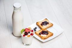 Mjölka flaskan och exponeringsglas med rostade bröd Royaltyfri Bild