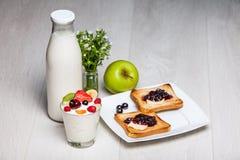Mjölka flaskan och exponeringsglas med rostade bröd Arkivfoton