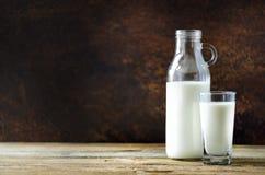 Mjölka flaskan och exponeringsglas på trätabellen, mörk bakgrund äta för begrepp som är sunt kopiera avstånd Royaltyfria Bilder