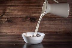 Mjölka häller in den vita plattan med sädesslag royaltyfria foton