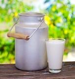 Mjölka i aluminiumburk och exponeringsglas. Arkivbilder