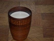 Mjölka i en kopp som göras av lera på en trätabell royaltyfria foton