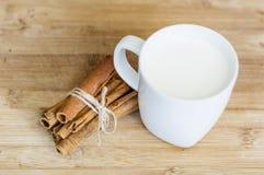 Mjölka i en vit kopp med kanelbruna pinnar på en träbakgrund Arkivfoton