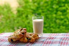 Mjölka i ett exponeringsglas och en bakning Arkivbilder