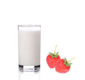 Mjölka i exponeringsglas och jordgubbar på vit bakgrund Arkivbild