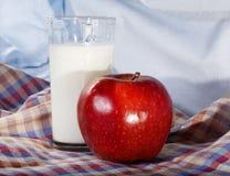 Mjölka i exponeringsglaset och det röda äpplet Arkivfoton