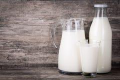 Mjölka i tillbringare, exponeringsglas och flaska på träbakgrund Royaltyfri Fotografi