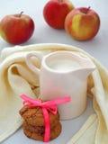 Mjölka, kakor och äpplen på vit träbakgrund Arkivbild