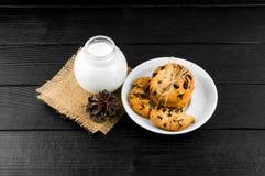 Mjölka kakor på en svart texturerad trätabell Royaltyfria Bilder