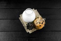Mjölka kakor på en svart texturerad trätabell Arkivfoton