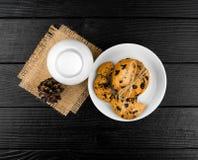 Mjölka kakor på en svart texturerad trätabell Fotografering för Bildbyråer