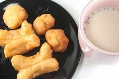 Mjölka med den friterade degpinnen Arkivbilder