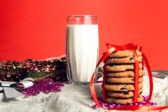 Mjölka och kakor på röd bakgrund för Santa Claus julen dekorerar nya home idéer för garnering till nytt år Royaltyfri Bild