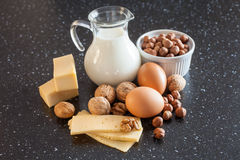 Mjölka, ost, ägg och muttrar på en tabell royaltyfria foton