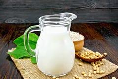 Mjölka sojabönor i tillbringare med mjöl på mörkt bräde arkivfoto