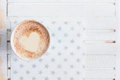 Mjölka te med hjärta som göras av kanel på en vit träbakgrund arkivbilder