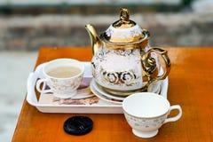 Mjölkakaffet har hällt in i koppen med en kokkärl fotografering för bildbyråer