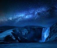 Mjölkaktig väg och fallande stjärnor över den Skogafoss vattenfallet i Island arkivbilder