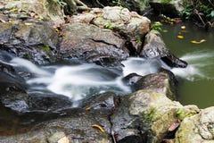 Mjölkaktigt flödande vatten och vaggar av vattenfallet Arkivbild